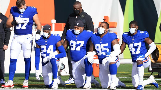 New York Giants players kneel wearing face masks during the National Anthem before the first half against the Cincinnati Bengals at Paul Brown Stadium on Nov. 29, 2020 in Cincinnati, Ohio.