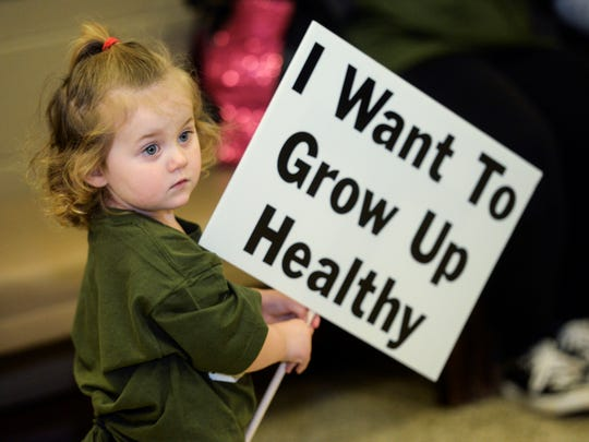 """Piper Bruner, 2, of Minden holds a protest sign while at a """"Stop the Burn"""" rally at the Minden Civic Center."""