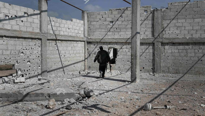 A Syrian rebel fighter patrols inside a building on the frontline against regime forces in the village of Bala on the outskirts of the capital Damascus, on February 28, 2016.