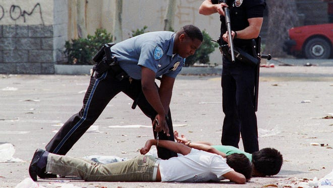 A Los Angeles police officer holds a shotgun on two looting suspects as a California State police officer puts them in handcuffs May 1, 1992, in South Central Los Angeles.