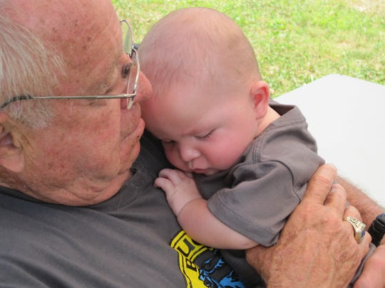 Earle Bruce holds his grandson Foster Poulton during