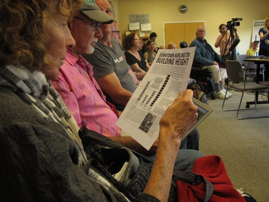 South Burlington resident Judith Rubenstein, left, looks at a flier opposing redevelopment plans for Burlington Town Center during a Burlington Planning Commission meeting on Tuesday. Rubenstein, who owns a property in Burlington, attended the meeting for a different item on the agenda.