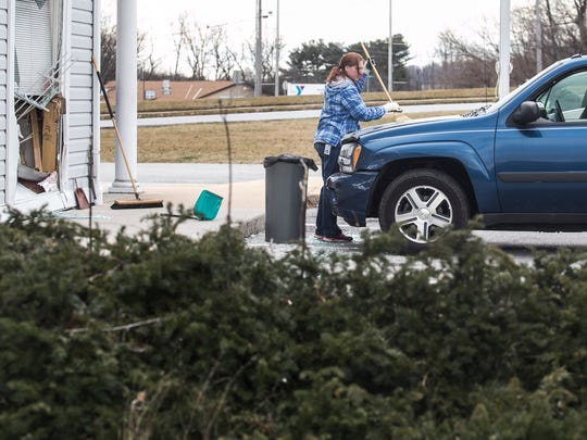 Custodian Melissa Kirstein, left, of Springettsbury Township, sweeps debris from an SUV that crashed into a window at the Shrewsbury post office at 50 Constitution Ave. on Wednesday, Feb. 15, 2017. Amanda J. Cain photo