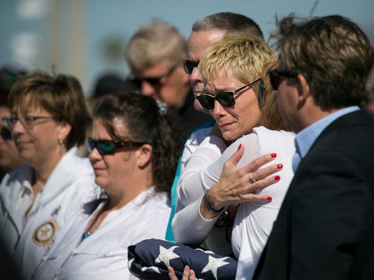 Lisa De La Cruz, center, hugs Beth Haely on Sunday, January 14, 2017, at Cypress Lake High School in Fort Myers. De La Cruz and Haely are the mothers of Sqt. Dylan Semolina and Cpl. Thomas Jardas, Marines who were killed in a helicopter collision off the north shore of Oahu in 2016.
