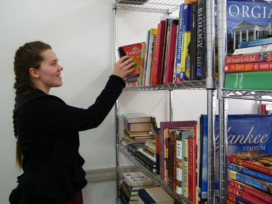 Addison Sherrell stocks a book at The Book Nook in downtown Green Springs.