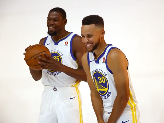 Kevin Durant #35 jokes with Stephen Curry #30 of the Golden State Warriors during the Golden States Warriors media day at Rakuten Performance Center on September 22, 2017 in Oakland, California.