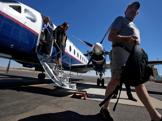 Passengers disembark from a Great Lakes Airlines plane