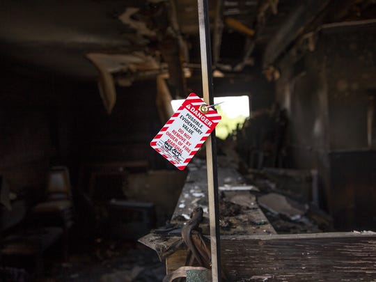 An evidence tag hangs from a window at  the closed Sage North Motel on Friday after an early-morning fire broke out at the structure.