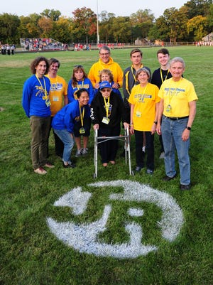 Redford Union honored the late Jimmy Rollin Friday night, unveiling his initials now stenciled into the turf at Hilbert Middle School. Here, the Rollin family gathers around the initials. In the center is his mom, Eleanor.