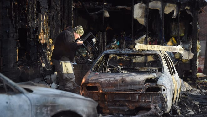 A Pennsylvania State Fire Marshal investigates the scene of a fatal fire in Shrewsbury Township Friday.