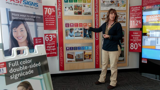 Kim Coufal, the franchise owner of FASTSIGNS in Farmington, talks on Monday about her new store, located at 5150 College Blvd., Suite 204.