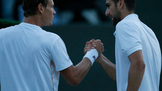 Marin Cilic of Croatia, right, shakes hands with Tomas Berdych of Czech Republic after defeating him in their men's singles match at the All England Lawn Tennis Championships in Wimbledon, London, Friday June 27, 2014. (AP Photo/Ben Curtis)