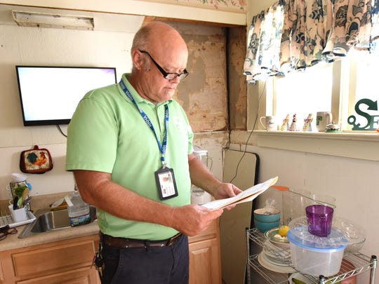 Scott Smith of First State Community Action Agency checks a home in Lincoln that was determined to have been painted with a material that contains lead.  Lead paint was banned in 1978, but remains in many older homes across the country.