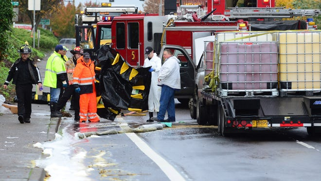 Officials clean up a spill on Wallace Road near Glen Creek in West Salem on Monday, Nov. 3, 2014.
