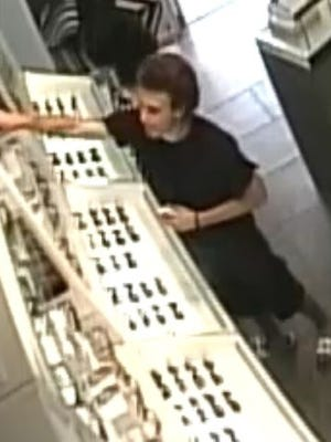 Surveillance image of a suspect in a Sunglass Hut robbery