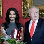 Austrian singer Conchita Wurst, left, winner of the Eurovision Song Contest, poses for photographs with Vienna Mayor Michael Haeupl after recieving the Golden Rathausmann, a medal for service to the city of Vienna.