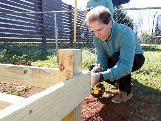 Alabama football coach Nick Saban works with Habitat