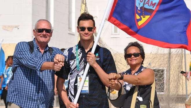 Benjamin Schulte, center, stands with parents Greg and Lou following the Oceania National Olympic Committee Flag Raising ceremony on Thursday in Copacabana, Brazil.