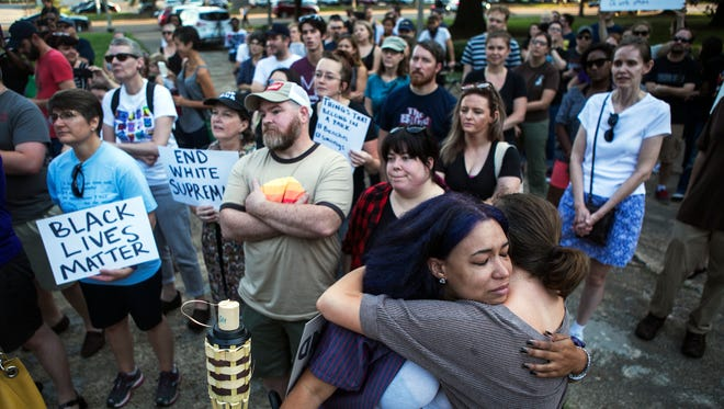 Theryn C. Bond center left, receives a hug from Taylor Cook as they stand in front of the Nathan Bedford Forrest statue in Health Sciences Park during a protest Aug. 12, 2017, showing support for those who were injured or lost their lives on Saturday in Charlottesville, Va.