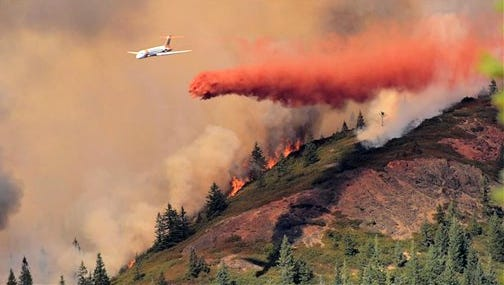In this Sunday, Sept. 14, 2014 photo provided by John Luerding, an air tanker drops fire retardant over a wild fire at the Rogue River-Siskiyou National Forest between Grants Pass and Cave Junction in Oregon. Two wildfires that started over the weekend were threatening scattered rural homes in western Oregon, where forests are critically dry and the weather is hot. (AP Photo/John Luerding)