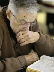 Lester Oestreich of Neenah reads his Bible during a session of the Fox Valley Bible Study Group.