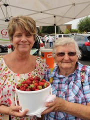 Shirley Brunson had reason to smile Saturday as she holds a big bucket of freshly picked strawberries at the Farmers Market at the Shoppes at EastChase. Alvin Benn/Special to the Advertiser.