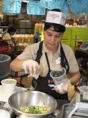 Tina of Los Altos Ranch Market prepares fresh guacamole.