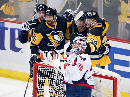 Pittsburgh Penguins Tom Kuhnhackl (34) celebrates his goal with his teammates behind Washington Capitals goalie Braden Holtby (70) during the first period of Game 3 in an NHL hockey Stanley Cup Eastern Conference semifinals in Pittsburgh, Monday, May 2, 2016. (AP Photo/Gene J. Puskar)