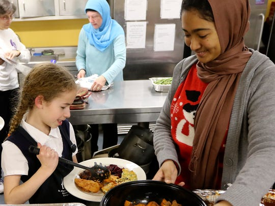 Naomi Ruttenberg, 11, of Englewood and Sarah Huq, 16, of Paterson put together a Christmas dinner plate at St. Paul's Community Development Corporation Emergency Men's Shelter in Paterson.  Both are members of the Sisterhood of Salaam Shalom, an interfaith group that was formed to help create peace.  Monday, December 25, 2017