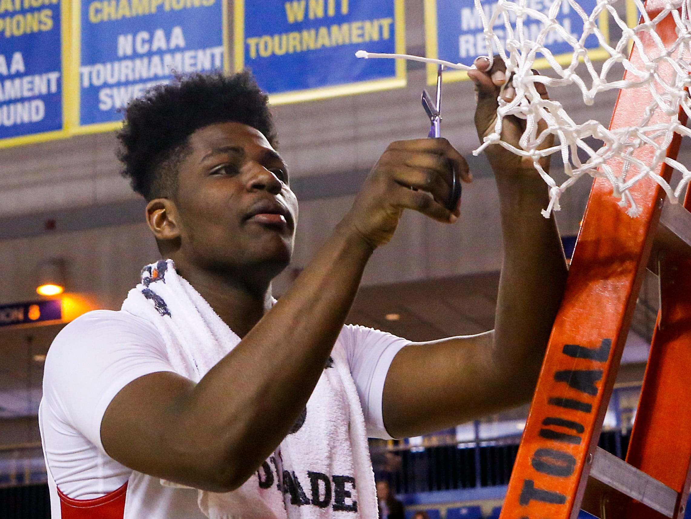 Smyrna's Jaymeir Garnett takes his piece of the net after the Eagles' 61-53 win in the DIAA state tournament title game at the Bob Carpenter Center on March 11.