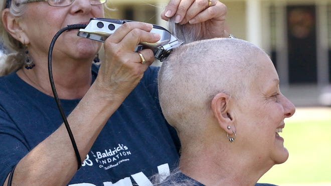 Louisville Elementary School teacher Janet Dougherty, right, smiles as her sister Pam Considine shaves the last tuft of hair from Dougherty's head while participating in the virtual head shaving St. Baldrick's Foundation cancer research fundraiser on team Constitution Cancer Crushers at the memorial bench for D.J. Patterson in Metzger Park in Louisville on Saturday, June 6, 2020.