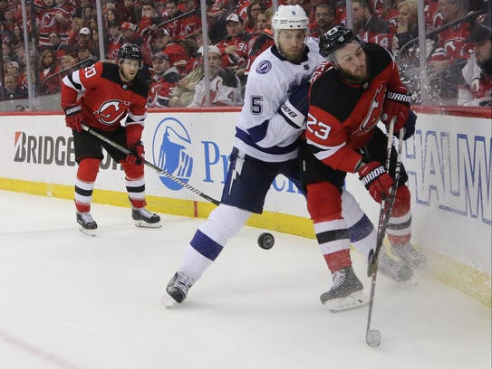 Dan Girardi of Tampa Bay checks Stefan Noesen of the