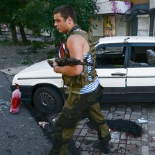 A pro-Russia rebel passes by a car that was hit by shrapnel from a shell in the town of Donetsk, eastern Ukraine, on Aug. 27.
