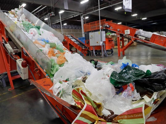 Conveyors carry mixed plastic into a device that will shred and recycle them at a plastics recycling plant in Vernon in January 2014.