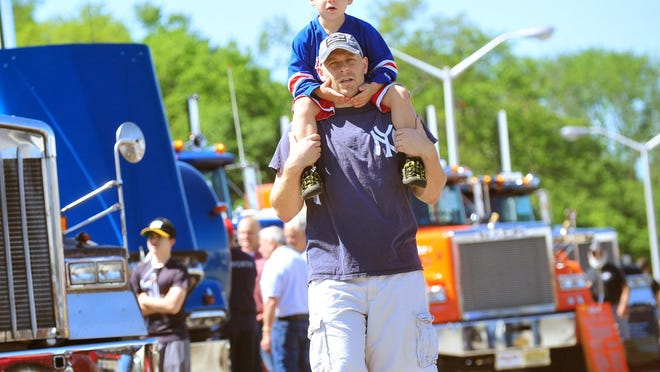 Brett Ulrich of Chatham gives his son Brody a better vantage point at the Annual Antique Truck Show Toy & Collectible Flea Market.