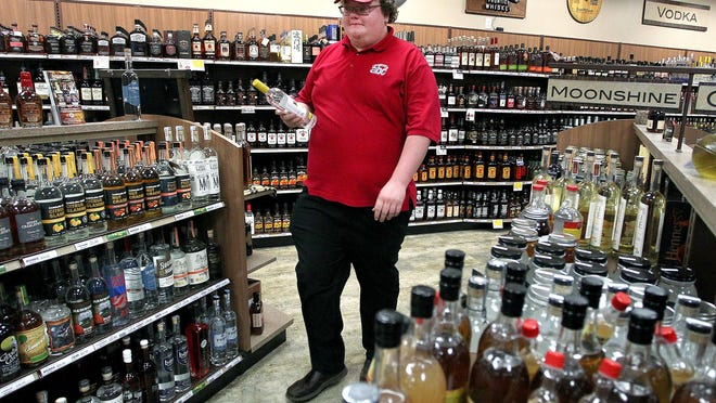 In this file photo from the spring, employee Casey Ham carries a customer's order to the counter at an ABC store in Gaston County. The Gastonia ABC Board saw its annual sales rise 15.4% in the fiscal year that ended June 30, to $13.8 million.