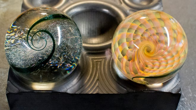 A pair of 2-and-a-half inch marbles by Miles Parker sit on a mold form that marble makers use to finish the spherical surfaces. The double hyperbolic paraboloid visible on the left marble is a signature marks of his work.
