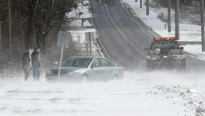 A stranded couple wait to get their vehicle towed near a snow drift that covered the surface of Millsboro Road near the Richland B&O Bike Trail on Tuesday.