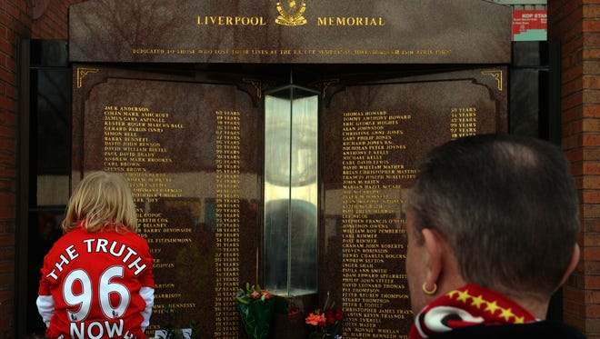 """In this file picture taken on April 15, 2013 a child wears a Jersey bearing the writing  """"Justice for the 96"""" in front of the Hillsborough Memorial at Liverpool FC's Anfield football ground in Liverpool, north-west England.  The British government was on April 25, 2014 investigating claims that official computers were used to post inflammatory comments about the Hillsborough stadium disaster on Wikipedia. Anonymous alterations to the online encyclopedia entry about the tragedy in which 96 Liverpool fans died were made from computers on the government's secure intranet, the Liverpool Echo reported."""