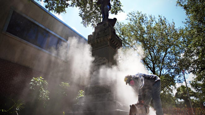 In an August 2017 photo, a concrete saw is used to remove the base of a Confederate monument, known by locals as Old Joe, near the corner of West University Avenue and South Main Street in Gainesville.