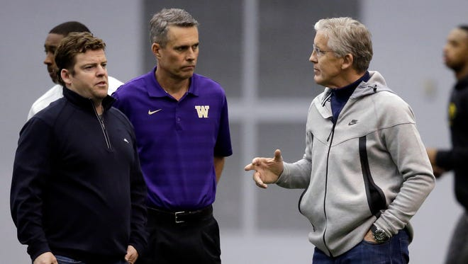 Washington head coach Chris Petersen, center, looks on with Seattle Seahawks' general manager John Schneider, left, and head coach Pete Carroll during a work out at Washington's pro day Thursday, April 2, 2015, in Seattle.