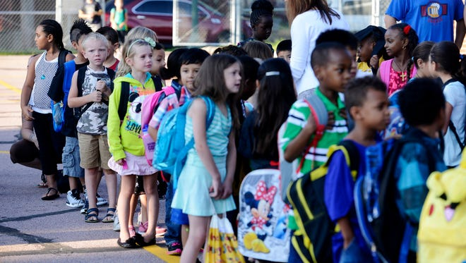 Aaron Singleton, 7 (camo shirt) and other 1st grade students line up before the first day of school at Longfellow Elementary School Monday, Aug 18, 2014.