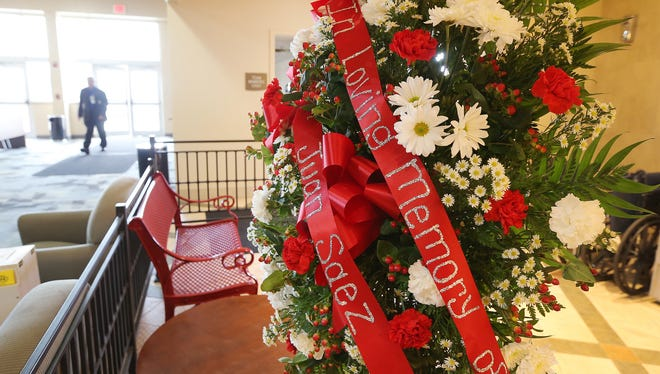 A memorial spray of flowers rests in the clubhouse at Indiana Grand Racing & Casino on Wednesday, Oct. 15, 2014, following the death of 17-year-old jockey Juan Saez, after he was injured in a racing accident Tuesday night. A security guard is shown walking through the closed clubhouse as racing was canceled at the Shelbyville facility because of the tragedy.