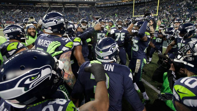 Seattle Seahawks players huddle on the field before an NFL football game against the Arizona Cardinals, Sunday, Nov. 15, 2015, in Seattle.