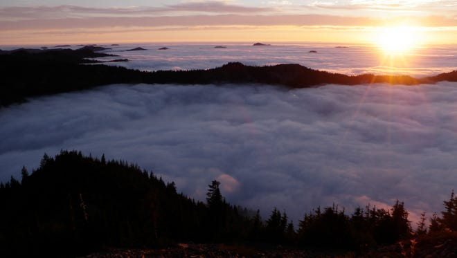 A blanket of clouds settle in the valley below Battle Ax at sunset.