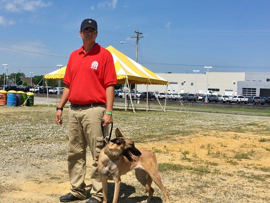 Verkie, a bomb-sniffing dog, stands with her handler