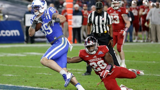 Duke's Braxton Deaver, left, scored a touchdown past Indiana's Will Dawkins during the second half of the Pinstripe Bowl last year.