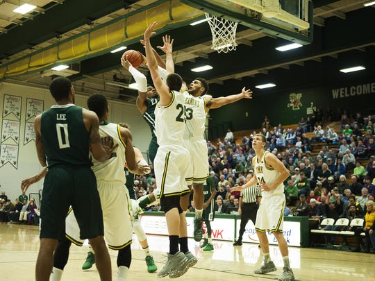 Vermont's Anthony Lamb (3) and Drew Urquhart (25) leaps to block the shot by Eastern Michigan's James Thompson IV (2) during the men's basketball game between the Eastern Michigan Eagles and the Vermont Catamounts at Patrick Gym on Saturday afternoon December 17, 2016 in Burlington.