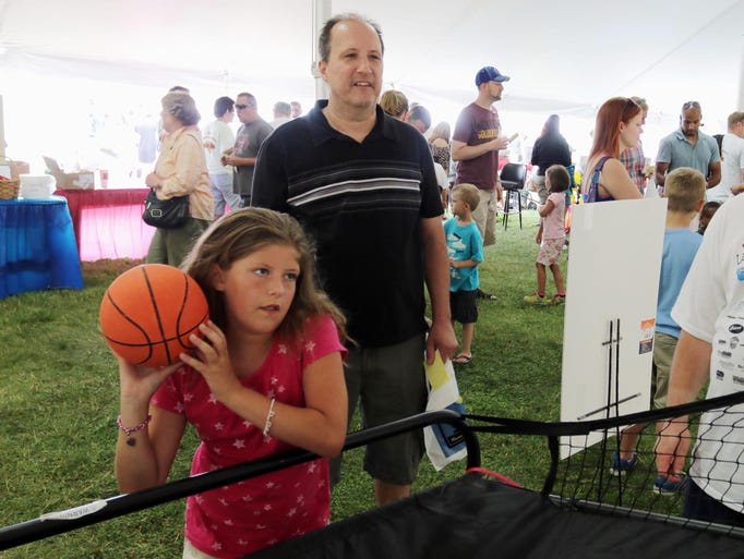 Ava Lazarewicz, 9, aims a basketball during Miesfeld's Lakshore Weekend Saturday July 26, 2014 at south pier in Sheboygan. Standing behind her is her dad Luke.