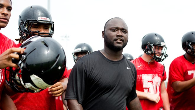 South Fort Myers Head Coach Anthony Dixon leads his team through its first practice of the season at South Fort Myers High School on Aug. 3, 2015.